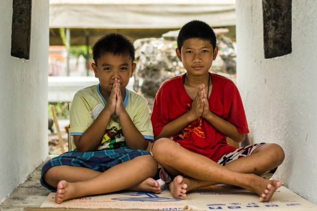 "Two young boys saying ""thank you"" in Thailand"